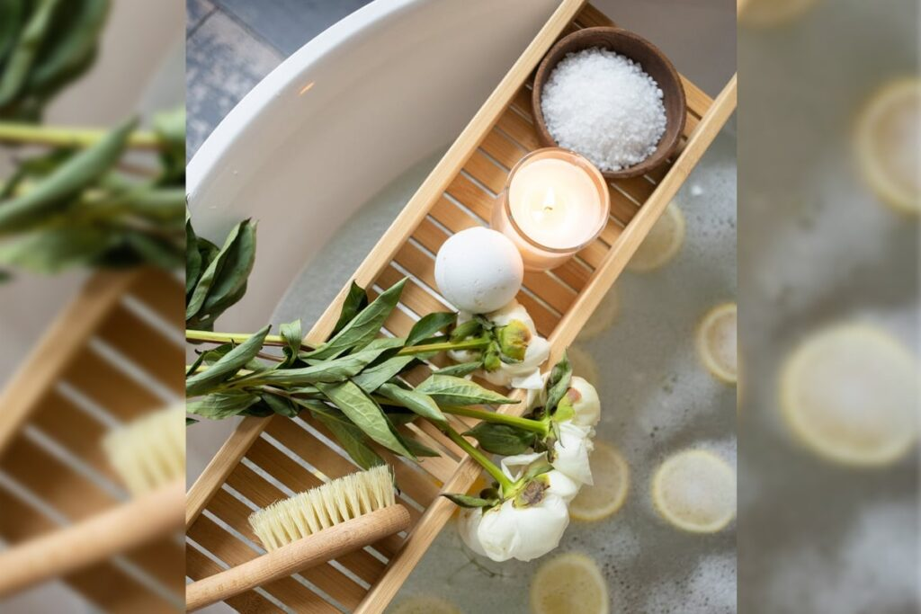 Wooden hair brush with flower, candle and salt on the top of bathtub