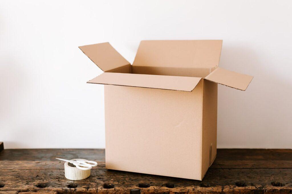 Cardboard Box besides scissors and tape